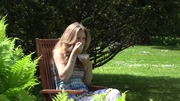 Portrét ženy jíst zmrzlinu na dřevěné židli v zahradě. 4k