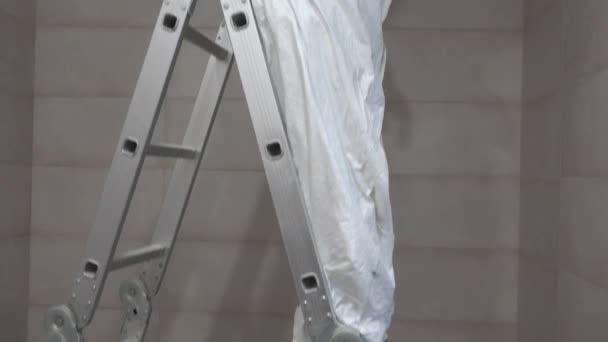 manuální pracovník viděla otvorem ve stropu sádrokartonu s pilkou