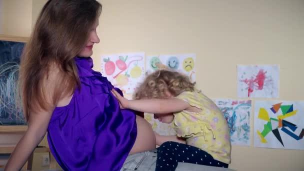 Aranyos gyermek lány csók viszket, és ölelés lány terhes nő anya has ül a kanapén