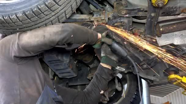 jiskry z mlýnek z nerezové oceli. mužské pracovník řezání rezavé auto díly.