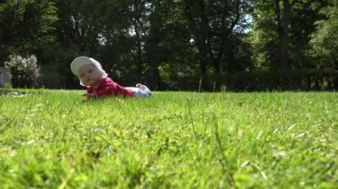 Small newborn baby lay on lawn grass and research it. 4K