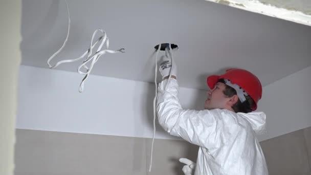 Kvalifikovaný dělník muže dělat sádrokartonové stropní otvory pro instalaci osvětlení