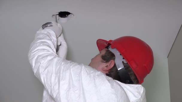 člověk dělat sádrokartonové stropní otvory pro instalaci osvětlení