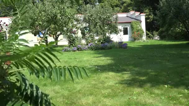 Obstbäume, Blumenbeete wachsen in gemauerten Gartenhäusern. 4k