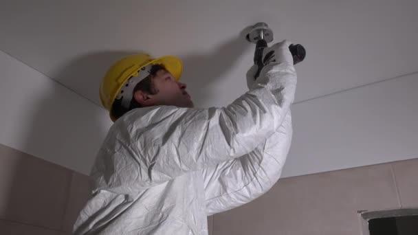 Kvalifikovaný dělník s přilbou, vrtání otvorů ve stropě