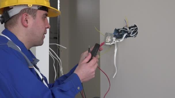 Muž s helmou testování socket s voltmetr
