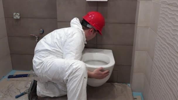 Berufsarbeitskraft mann hängen schwere wc beckens schüssel in