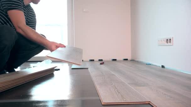 Pokládka podlahy s laminované podlahoviny desky proti světlu okno mladý dělník
