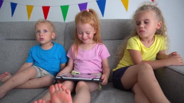 Přátelé děti hrát hry na tabletu počítače sedí na pohovce. pohyb fotoaparátu