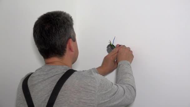 Kvalifikovaný elektrikář nainstalovat elektrickou zásuvku se šroubovákem