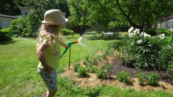 4 years old girl spraying grandmother flower bed with water sprinkler. Gimbal