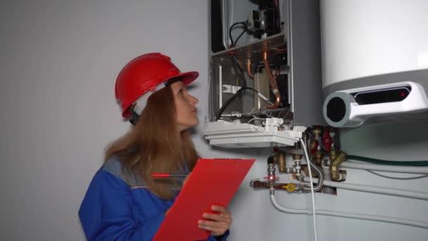 Ženský technik provádět údržbu topného kotle v soukromém domě