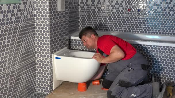 Klempner lächelt in Kamera und zeigt Finger nach oben auf Toilettenschüssel