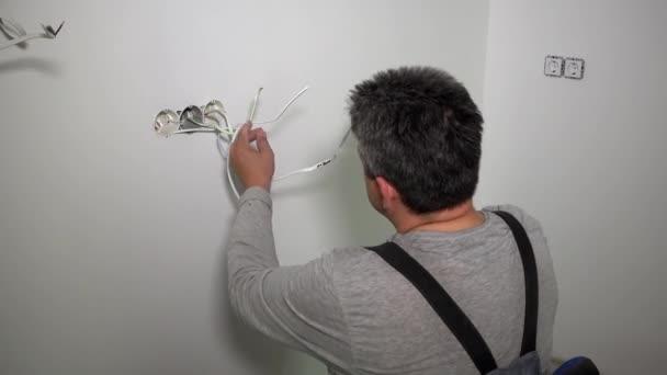 Elettricista uomo con indicatore tester di controllo cavi per cavi di corrente