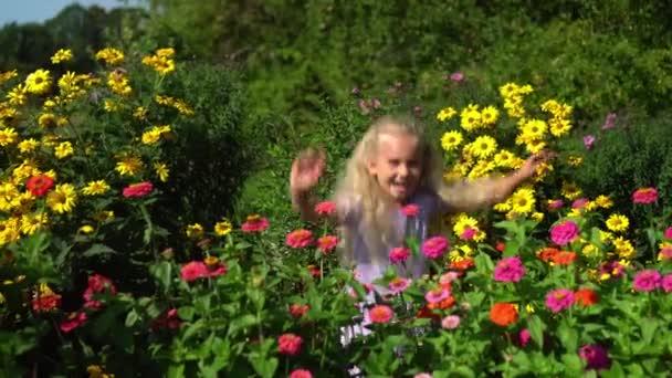 Excited preschooler girl hiding over colorful flower beds in summertime garden