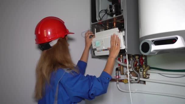 Professionelles Arbeitermädchen, das den Gaskessel für Warmwasser und Heizung wartet