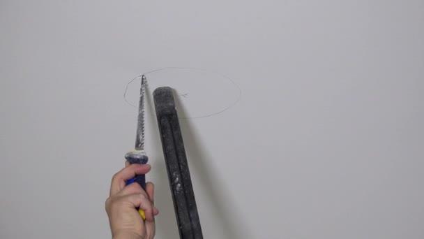 Pracovník ruka s ruční pilou a vysavač pilový otvor v sádrovém stropě