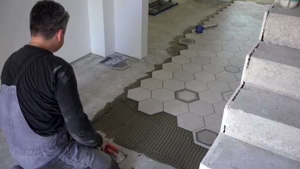 Kvalifikovaný tiler aplikovat lepidlo a položit šestiúhelník tvar dlaždice u schodů