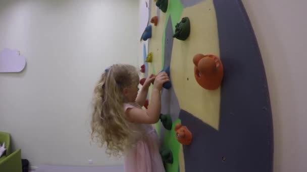 Charming Girl in Pink Dress Has Fun On The Climbing Wall. Gimbal shot
