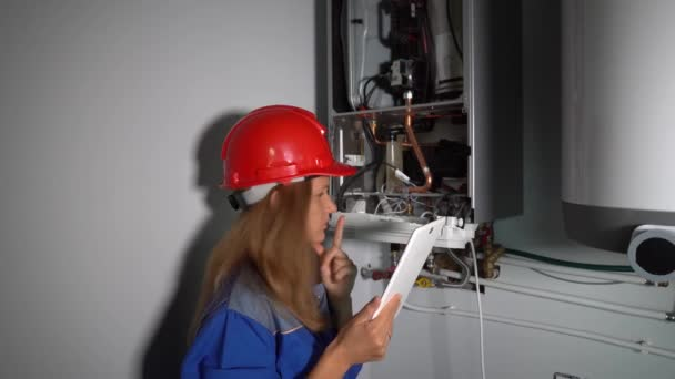 technician girl inspecting gas boiler heating system with tablet computer