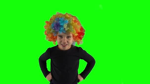 Dühös lány színes bohóc parókával a kamerába néz. Gyermeknegatív érzelem
