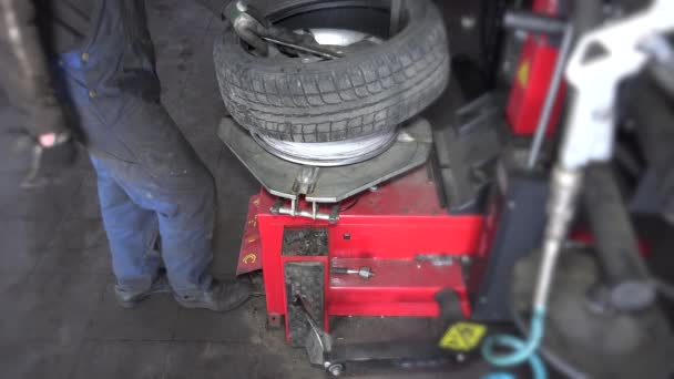 férfi kiegyensúlyozó kerék a kiegyensúlyozó autó javítás műhely. 4k