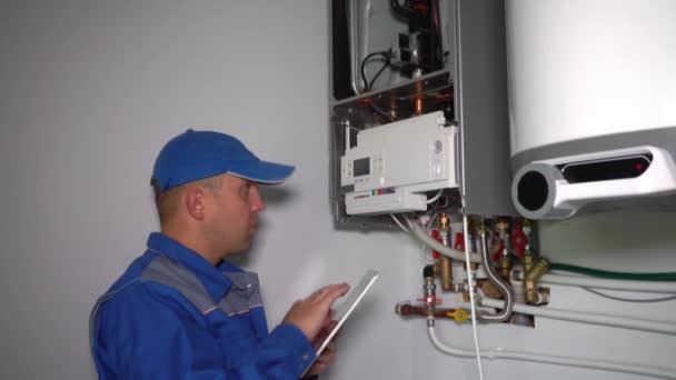 Mann repariert Gasheizung mit Tablet-Computer