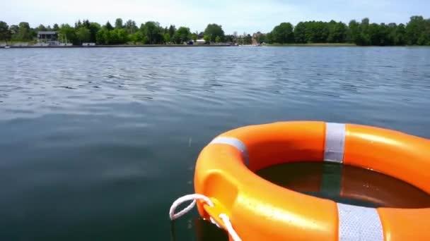 Orangefarbene Rettungsboje, die weit von der Küste entfernt auf dem Seewasser schwimmt. Gimbal-Bewegung