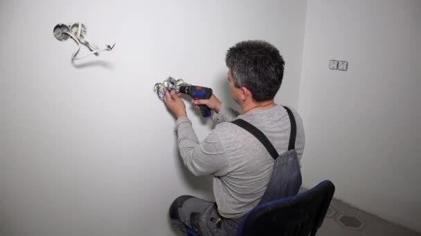 Muž pracující na elektrické zásuvce drátů pomocí bezdrátového šroubováku vrták