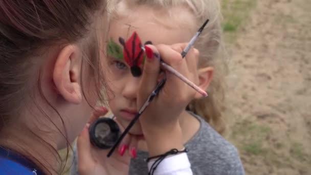Děti malují na obličej. Umělec maluje holčičku jako berušku. Gimbalův pohyb