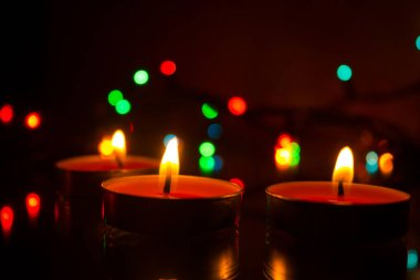 On a dark background a candle made of wax and a garland