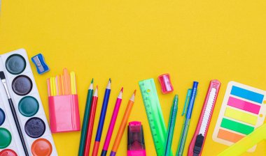 Office supplies on a yellow background. Various school supplies on a bright yellow background. Text frame with office supplies. The layout of the school. Welcome back to school. Concept of advertising office supplies. Flat lay with space for text.