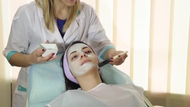 Mladá žena v lázních s obličejové masky. Žena ve spa salonu