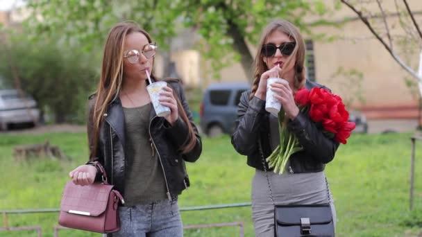 dvě holky kamarádky v sluneční brýle drink mléčné koktejly na ulici