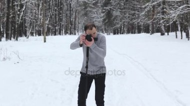 a guy in a snow-covered forest shoots a video