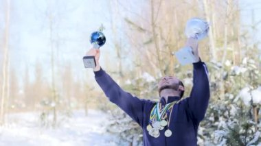 young guy sportsman rejoices with cups and medals