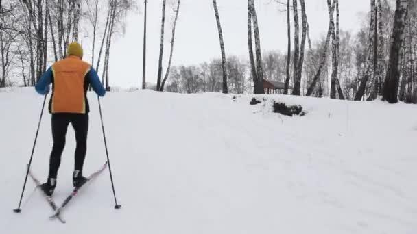 Ein Sportler auf Skiern erklimmt einen schneebedeckten Berg