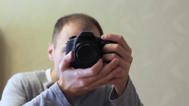 Fiatal srác fotós egy fényképezőgéppel a tükör tükrében.