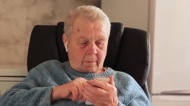 Elderly woman with a mobile device and airpods