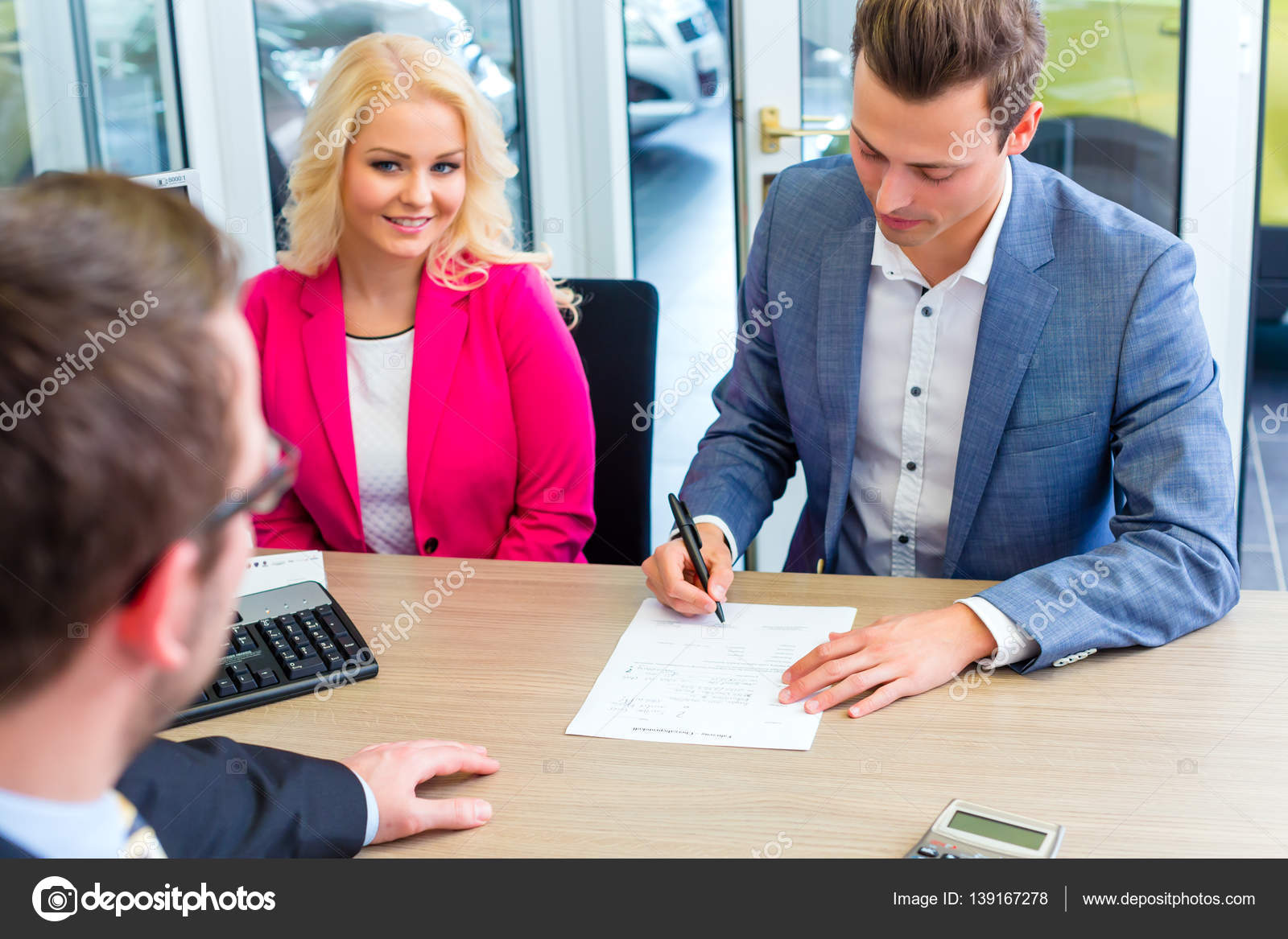 man signing sales contract for auto at car dealership stock photo