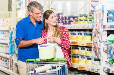 Couple in hardware store arguing about color of paint for renova