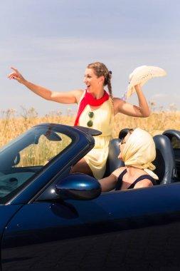 friends having summer joyride in convertible car