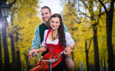 """Картина, постер, плакат, фотообои """"Пара в дирндль и кожаные брюки вместе на велосипеде"""", артикул 139166676"""