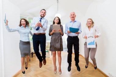 Group of women and men in office jumping