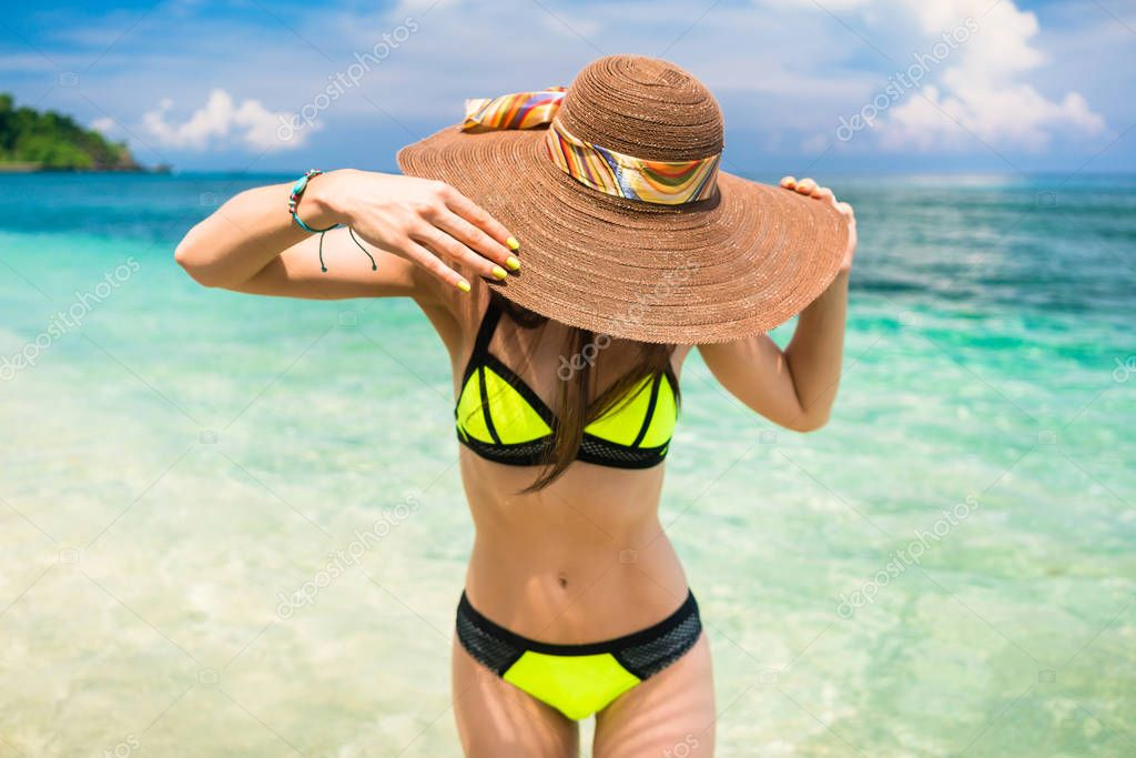 Woman on vacation wearing beach hat bathing in ocean