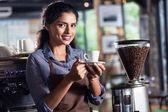 Fotografie indischer Barista bietet Kaffee an
