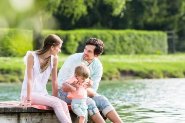 Happy family sitting on jetty on lake or pond