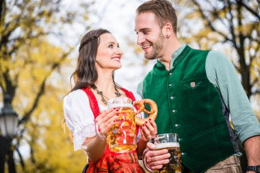 Couple in Dirndl and Tracht having Pretzel and Bier