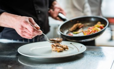 Chef finishing food on plate in restaurant kitchen