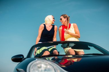 Woman having summer trip in convertible car